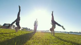 Jonge vrouwen die acrobatisch wiel op het gras uitvoeren, silhouet die van de jonge mens zich in centrum van hen bevinden stock footage