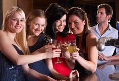 Jonge vrouwen die bij staaf drinken stock fotografie