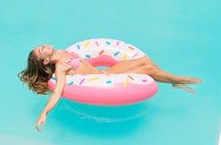 Jonge vrouwen die in bikini op een opblaasbare doughnut in zwembad liggen Het meisje geniet van zonnebadend op drijvend pool opbl royalty-vrije stock afbeelding
