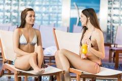 Jonge vrouwen die door de pool ontspannen Royalty-vrije Stock Afbeelding