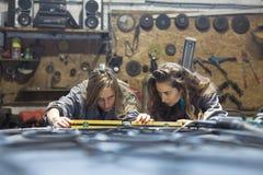Jonge vrouwen die in een mechanische winkel werken stock fotografie