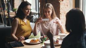 Jonge vrouwen die foto van maaltijd in koffie nemen die met smartphonecamera schieten stock videobeelden