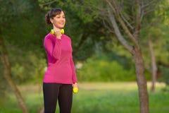 Jonge vrouwen die gewichtheffen in openlucht in het park doen Stock Foto's