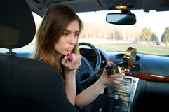 Jonge vrouwen die haar samenstelling in auto voorbereiden Stock Foto
