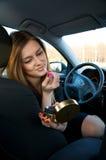 Jonge vrouwen die haar samenstelling in auto voorbereiden Royalty-vrije Stock Afbeeldingen