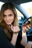 Jonge vrouwen die haar samenstelling in auto voorbereiden Stock Afbeeldingen