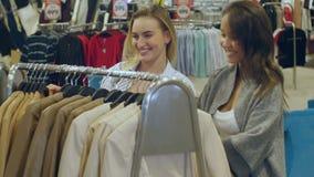Jonge vrouwen die kleren kiezen die op de rekken hangen stock footage