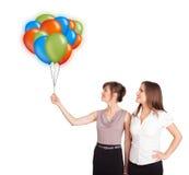 Jonge vrouwen die kleurrijke ballons houden stock afbeelding