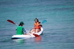 Jonge vrouwen die onderaan een overzees kayaking Royalty-vrije Stock Foto's