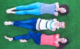 Jonge vrouwen die op groen gras liggen Royalty-vrije Stock Foto's