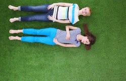 Jonge vrouwen die op groen gras liggen Jonge vrouwen Royalty-vrije Stock Afbeeldingen