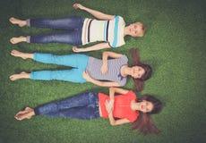 Jonge vrouwen die op groen gras liggen Jonge vrouwen Royalty-vrije Stock Foto's