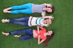 Jonge vrouwen die op groen gras liggen Jonge vrouwen Stock Fotografie