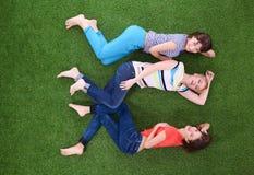 Jonge vrouwen die op groen gras liggen Jonge vrouwen Stock Foto's