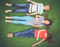 Jonge vrouwen die op groen gras liggen Jonge vrouwen Royalty-vrije Stock Fotografie