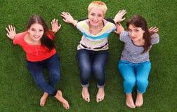 Jonge vrouwen die op groen gras zitten Royalty-vrije Stock Afbeelding