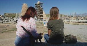 Jonge vrouwen die op ruïnes letten, terwijl het zitten op de steen in Oude stad Perge, op openlucht antiek historisch museum