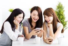 jonge vrouwen die op slimme telefoon in woonkamer letten Stock Afbeeldingen