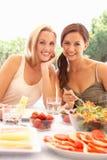 Jonge vrouwen die in openlucht eten Stock Afbeelding