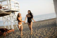 Jonge vrouwen die pret hebben bij het strand stock afbeeldingen