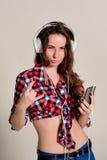 Jonge vrouwen die pret hebben, die aan muziek met hoofdtelefoons luisteren Royalty-vrije Stock Foto's