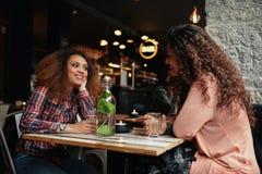 Jonge vrouwen die in restaurant het spreken zitten Stock Foto