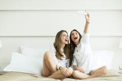 Jonge vrouwen die selfie in het bed nemen Stock Afbeelding
