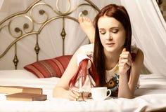 Jonge vrouwen die thee drinken en een boek op een bed thuis lezen Stock Fotografie