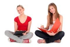 Jonge vrouwen die thuiswerk doen stock foto