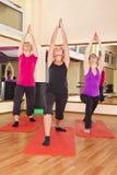 Jonge vrouwen die uitrekkende oefeningen in gymnastiek uitvoeren Stock Afbeeldingen