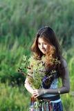 Jonge vrouwen die wildflowers houden Stock Afbeeldingen
