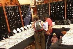 Jonge vrouwen die zilveren juwelen Inca kiezen Stock Foto's