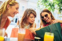 Jonge vrouwen in een koffie na het winkelen stock foto
