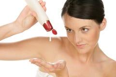 Jonge vrouwen gietende lotion ter beschikking Royalty-vrije Stock Afbeeldingen
