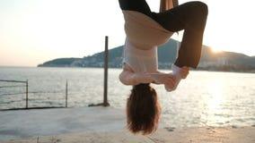 Jonge vrouwen hangende bovenkant - neer in hangmat op kust in openlucht stock footage