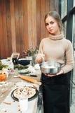 Jonge vrouwen kokende pastei met droge vruchten stock foto's