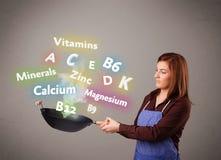 Jonge vrouwen kokende vitaminen en mineralen Royalty-vrije Stock Afbeeldingen