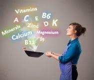 Jonge vrouwen kokende vitaminen en mineralen Royalty-vrije Stock Foto