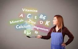 Jonge vrouwen kokende vitaminen en mineralen Stock Fotografie