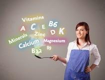 Jonge vrouwen kokende vitaminen en mineralen Stock Afbeelding