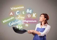 Jonge vrouwen kokende vitaminen en mineralen Stock Foto's