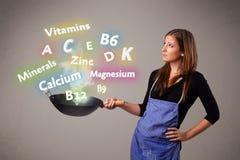 Jonge vrouwen kokende vitaminen en mineralen Royalty-vrije Stock Foto's