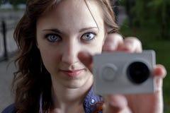Jonge vrouwen met in hand close-up van de actiecamera Stock Afbeeldingen