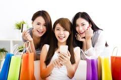 jonge vrouwen met het winkelen zakken en het bekijken slimme telefoon Royalty-vrije Stock Afbeeldingen