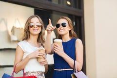Jonge vrouwen met het winkelen zakken en koffie bij winkel Stock Foto
