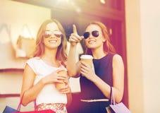 Jonge vrouwen met het winkelen zakken en koffie bij winkel Royalty-vrije Stock Afbeelding