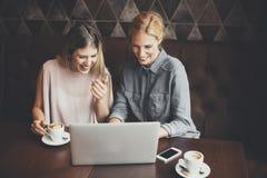 Jonge vrouwen met laptop in de koffie Stock Foto