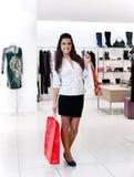 Jonge vrouwen met pakketten in de winkel Stock Foto
