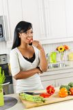 Jonge vrouwen proevende groenten in keuken royalty-vrije stock afbeeldingen