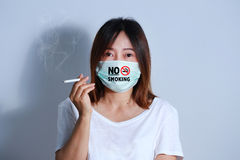 Jonge vrouwen rokende sigaret met beschermend masker Stock Fotografie